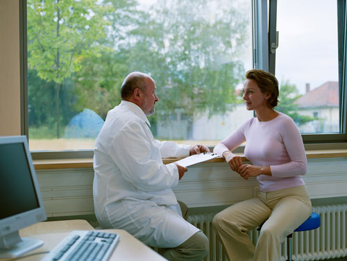 A woman talking with her dentist about receiving an oral biopsy.